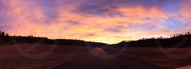 road along open field on sunset photo