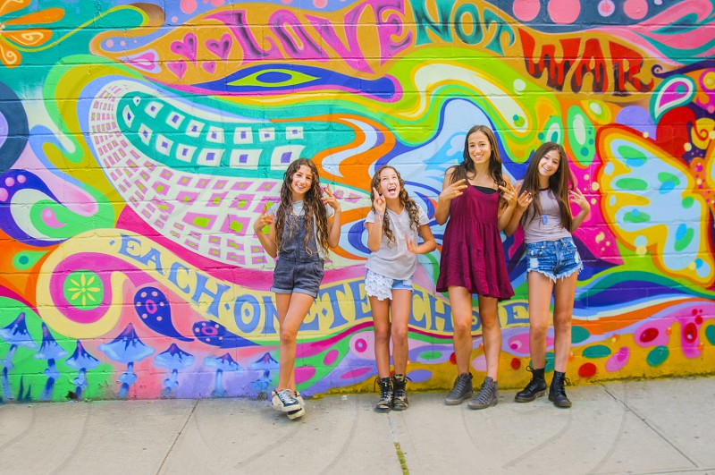 4 long haired girls standing by the graffiti wall photo