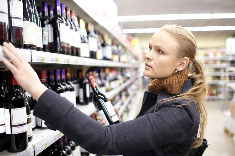 Young woman is choosing wine in the supermarket. photo