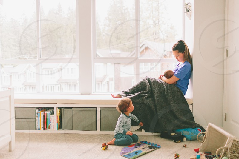 A nursing mother sitting in the window with her baby while her son plays on the floor.  photo