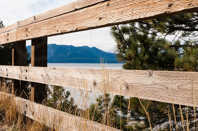 Lake and mountain view through rustic fence photo