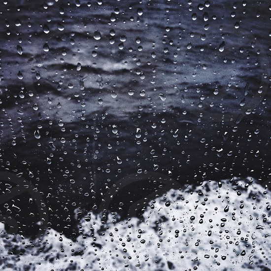 water drops on a window close to waves crashing in blue water photo