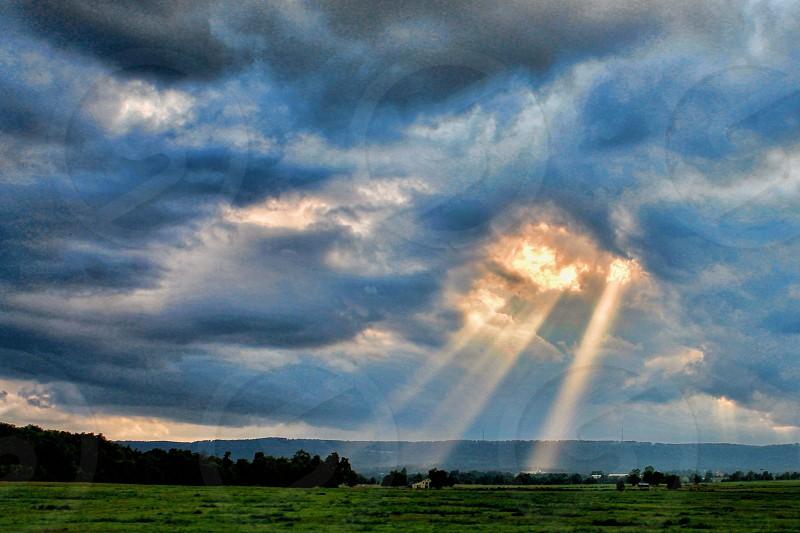 Sunbeams stream through gray storm clouds. photo