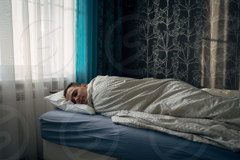 Morning. Light from window. Men sleep in bed under the blanket photo