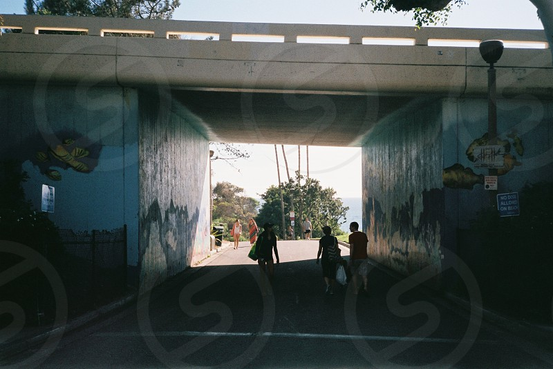 people carrying bags walking through tunnel under overpass bridge with painted murals against bright sky photo