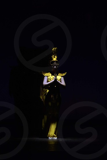 Elegant black and yellow gold traditional ethnic Chinese dancer on stage in the spotlight photo
