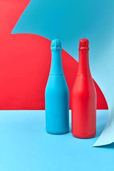 Two creative wine mock-up bottles painted spray red and blue on a duotone wavy background with place for text. photo