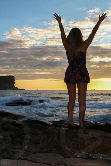 Blonde Woman Wearing Colorful Romper Standing Next to Ocean Water photo