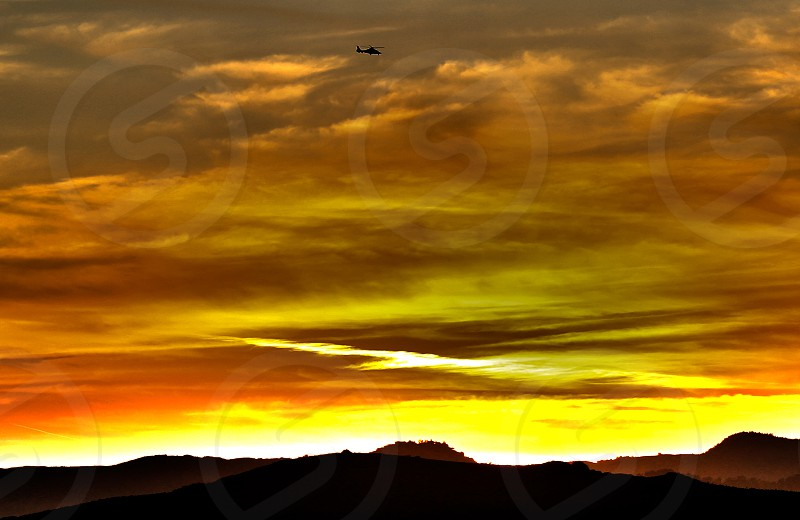 Helicopter flying high above the mountains. Fiery sky. photo