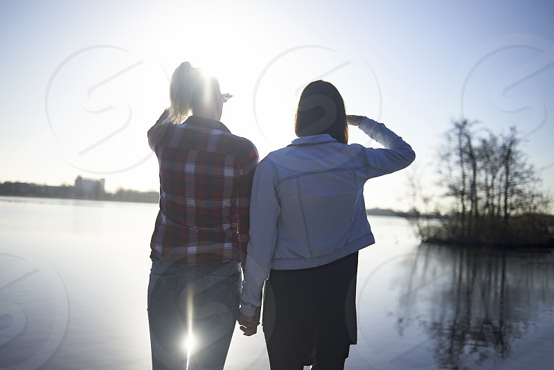 A young lesbian couple from behind  standing at a lake shore looking at the lake into the sunshine photo