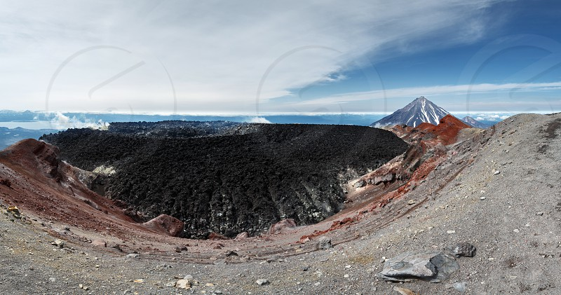Beautiful panoramic volcanic landscape of active volcano of Kamchatka Peninsula: view of crater Avachinsky Volcano on background scenic cone Koryak Volcano on a sunny day. Russia Far East Kamchatka. photo