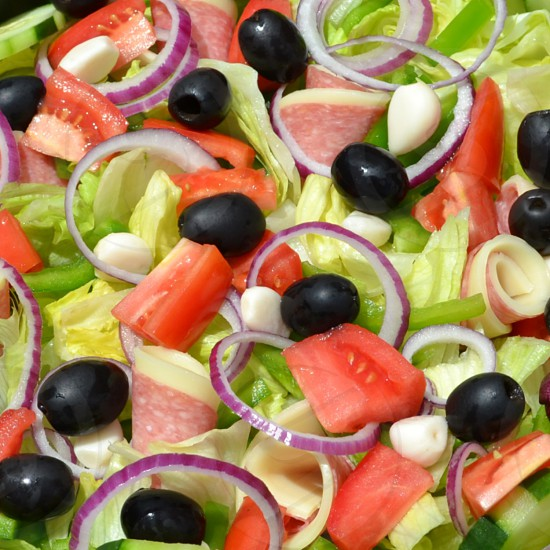 closeup of antipasto salad with lettuce tomatoes black olives red onions pickled garlic cloves provolone cheese and salami photo