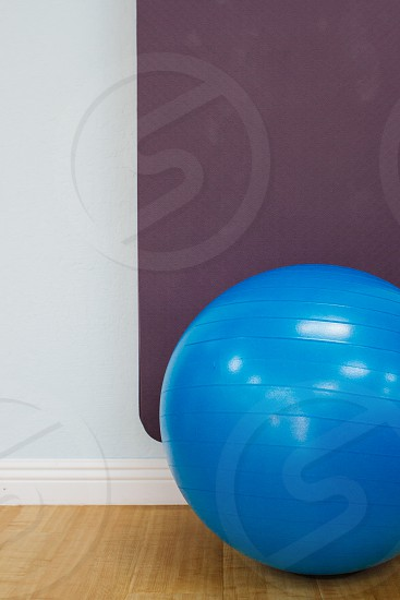 blue stability ball behind purple textile on brown wooden parquet floor photo