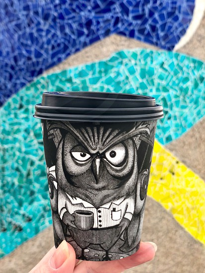 Walk around Barcelona.  Disposable paper coffee cup in hand on mosaic background. Personal perspective.  photo