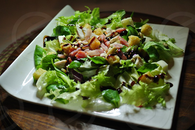 Delicious Caesar salad with bacon bits pine nuts balsamic vinegar and caesar sausage photo