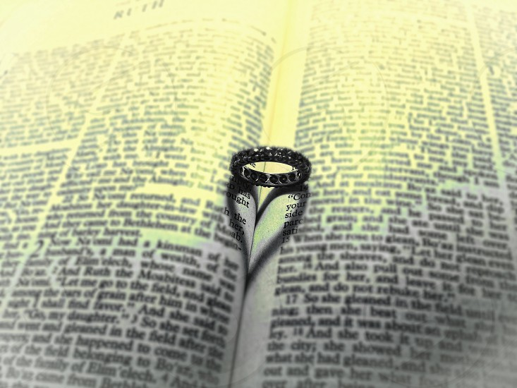 Diamond wedding rind forms a heart shdows inside the pages of an open bible photo