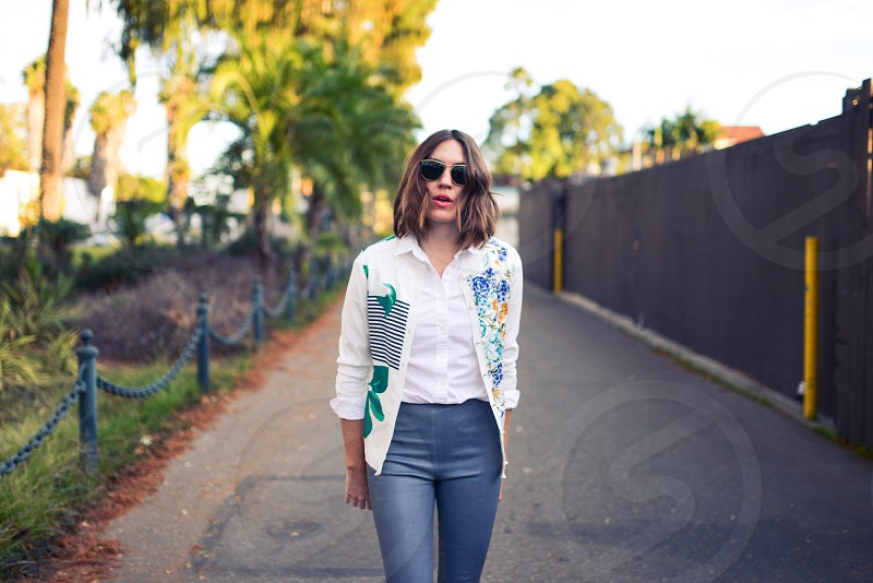 woman in white button down shirt and blue leather pants walking down sidewalk photo
