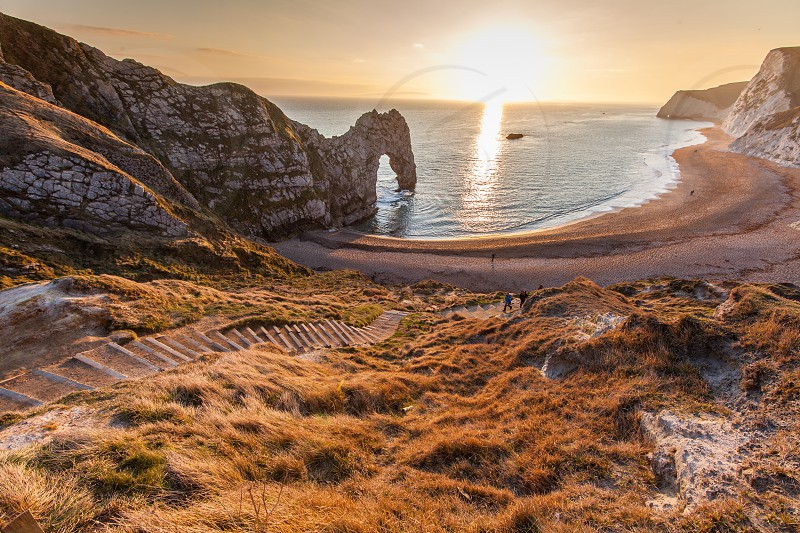 Sunset at Durdle Door on the Jurassic coast of Doset England in the uk featuring a natural geolicaly formed arch over the sea and steps leading down to the beach photo