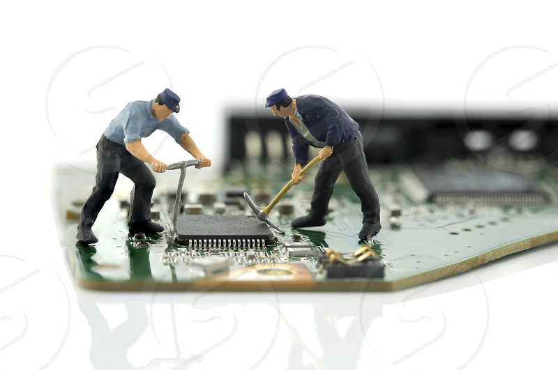 little world two man repair chips on computer motherboard photo