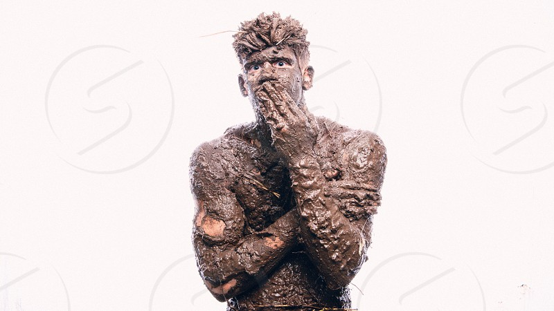 A young man covered in mud and dirt like he just came from a mudding trip or a mud marathon. He looks like a surprised or curious guy.  photo