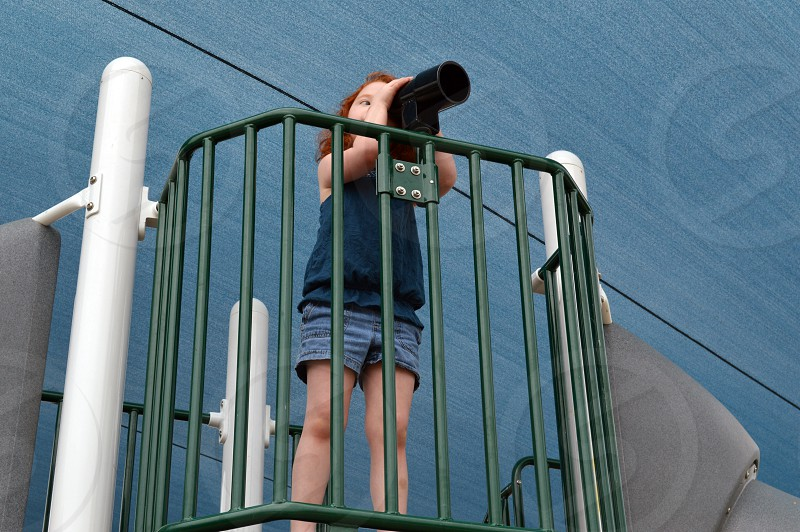 Young girl with red hair looking through the play telescope on a playground. photo