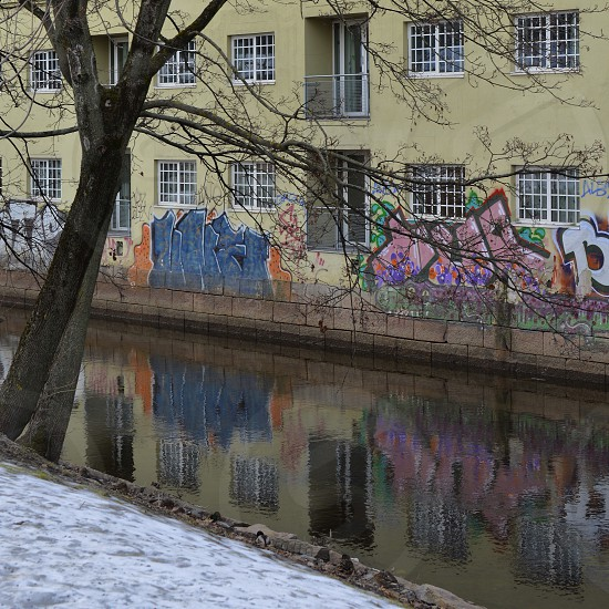 City charm graffiti water tree city snow building reflection  photo