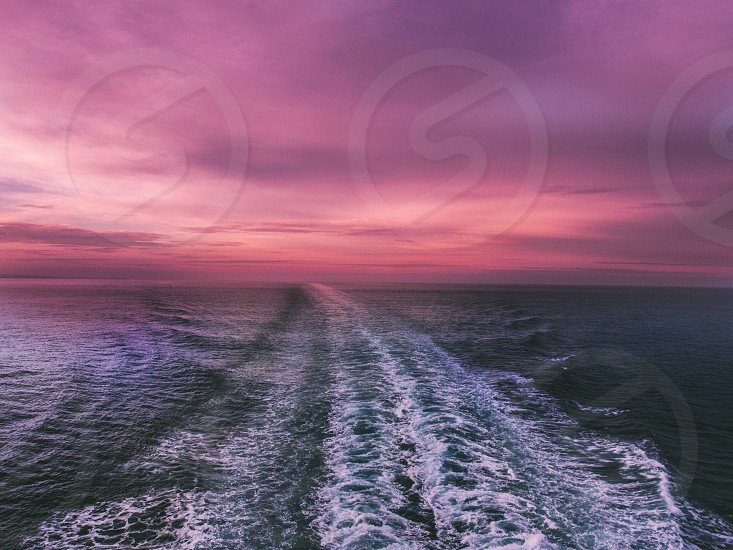 purple sky over a boat making a wake in the water photo