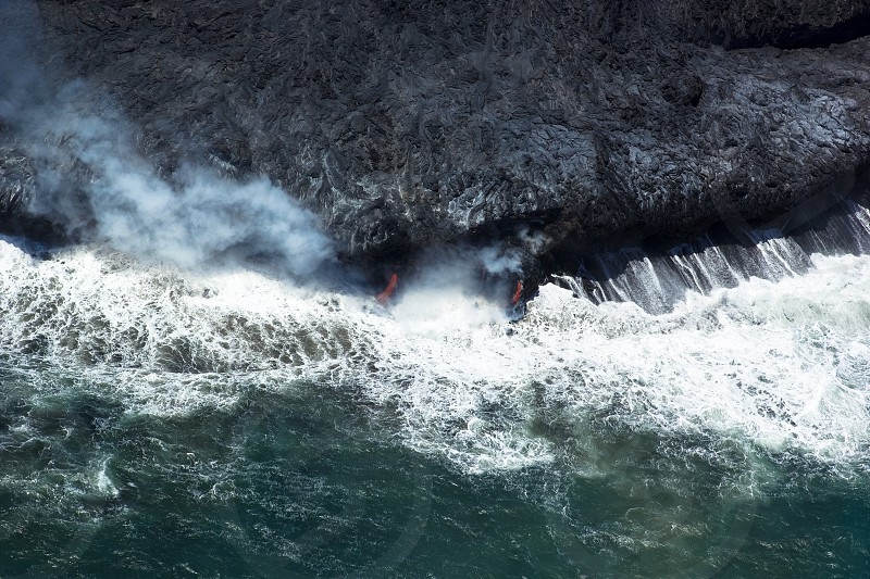 Hot lava spilling into the ocean on Hawaii. photo