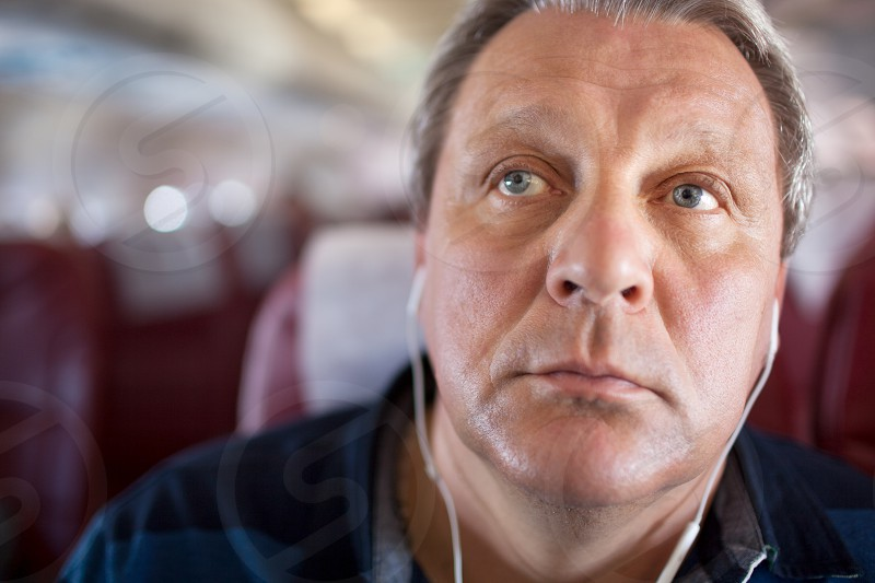 Close-up shot of a mature man spending time with music in the airplane. He listening favourite songs in earphones photo