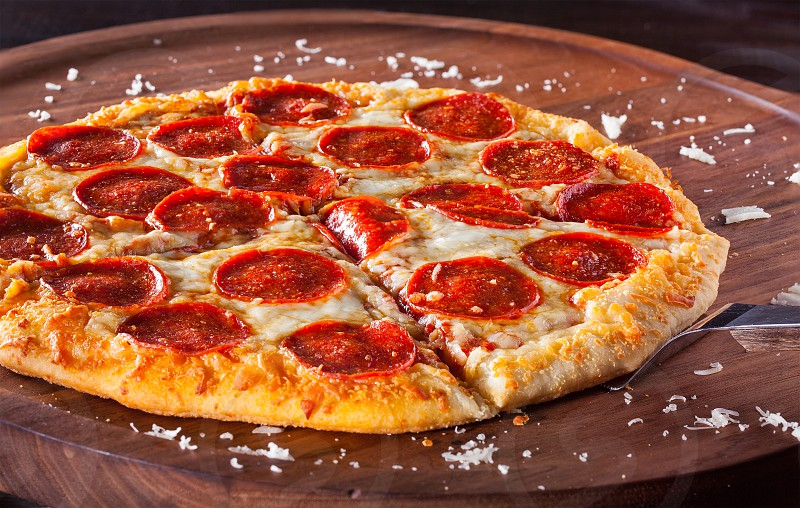 Hot homemade pepperoni pizza with cheese shavings on a wooden surface photo