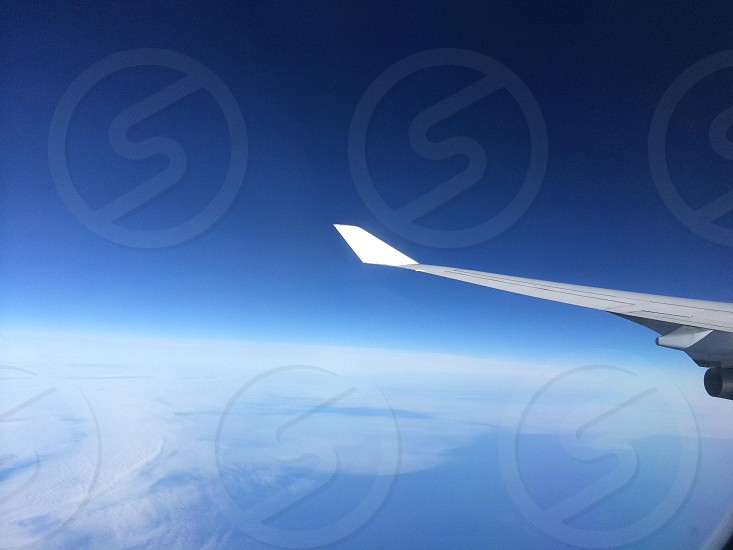 white aircraft wings flying over white clouds and blue body of water photo