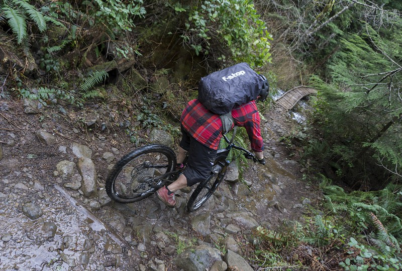Photographer riding a mountain bike with a photopack on a rocky trail in southwest Washington. photo