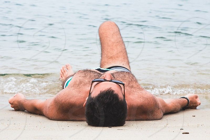 Young man lying on the beach by the water photo