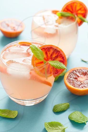 Blood orange cocktail with slices of orange on turquoise background photo