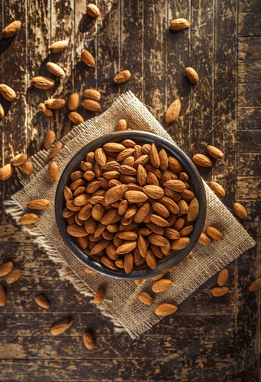 Raw Almonds on Burlap and Wooden Surface photo