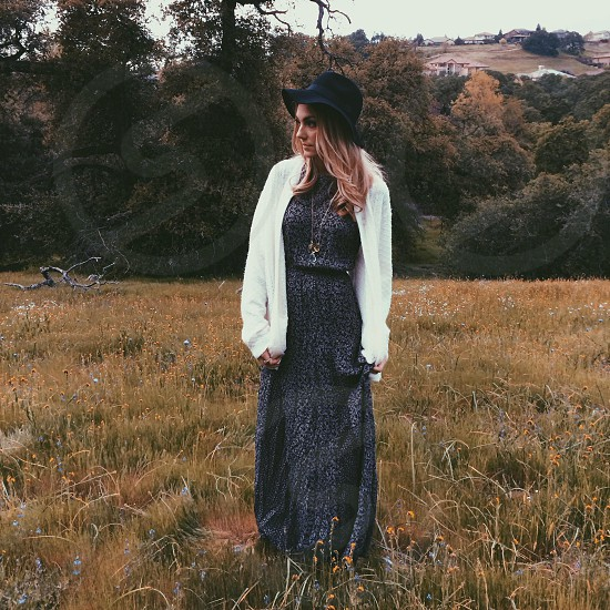 woman in black dress and hat with long sleeve white sweater in field  photo