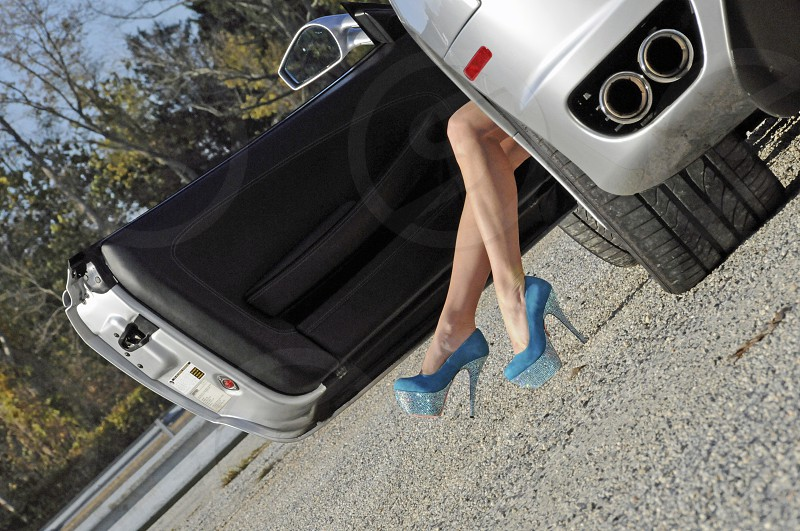 woman's legs out of car photo