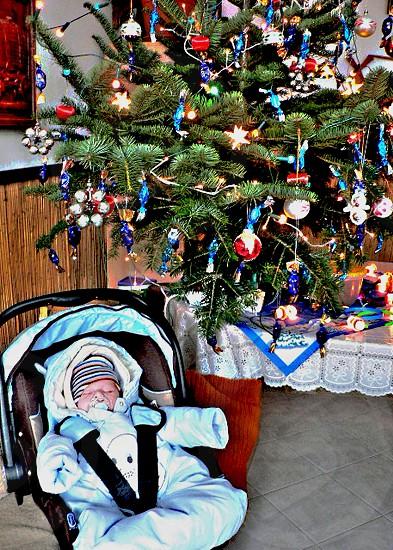Sleeping baby under the Christmas tree. photo