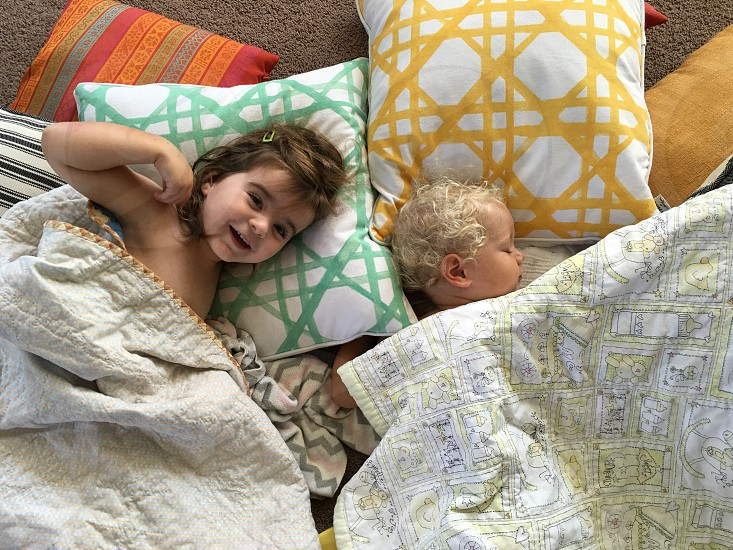 2 baby lying on the bed covered by white and yellow blanket photo