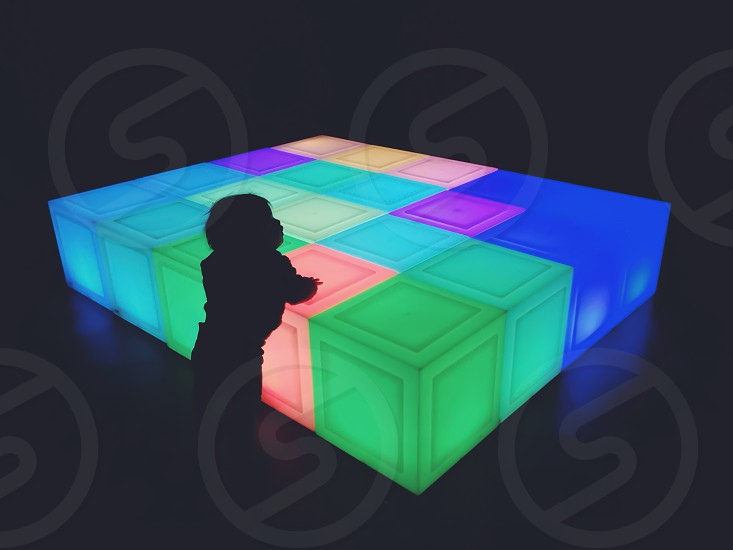 silhouette of toddler leaning on cube with green orange blue and yellow lights photo