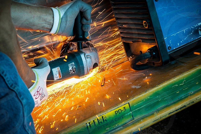 A man makes sparks while grinding a piece of metal for an art installation.  (Logos removed or changed.) photo