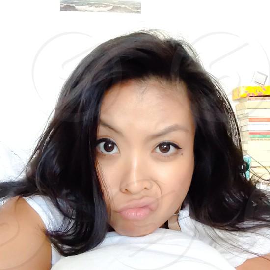 woman in white short sleeve shirt smirking at camera photo