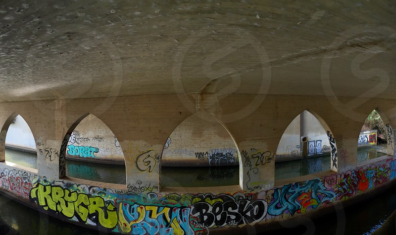 Graffiti contrasts the crisp architecture found under the bridge in the Pacific Coast Highway. The bridge allows pedestrians to pass from the east side of the PCH to the beach in Malibu California.  photo