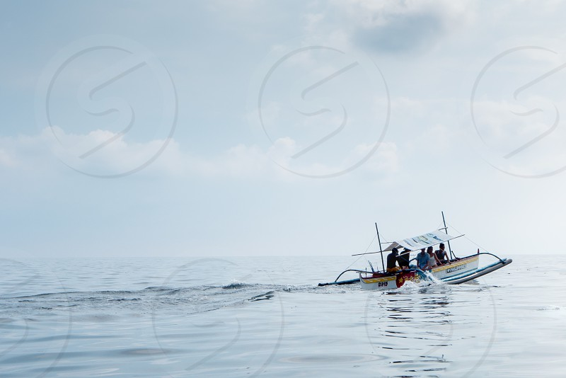 people riding  motorboat on body of water photo