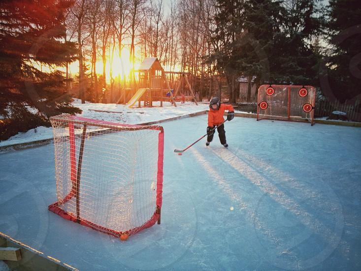 Ice hockey on backyard rink at sunset  photo