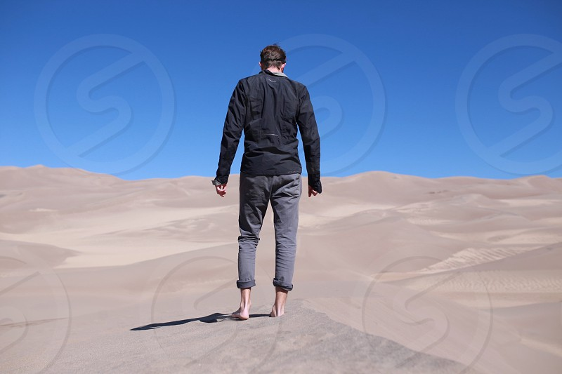 man in black long-sleeved shirt and pants on dessert under blue sky photo