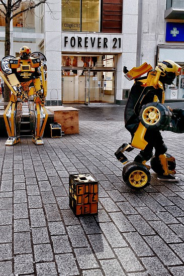 2 person wearing bumblebee from transformers costume standing on sidewalk beside leafless tree in front of forever 21 store during daytime photo