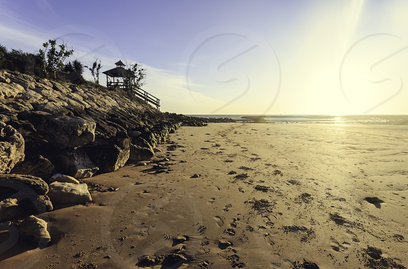 Pier on the seawall on the beach of Sanlucar de Barrameda and footprints in the sand photo