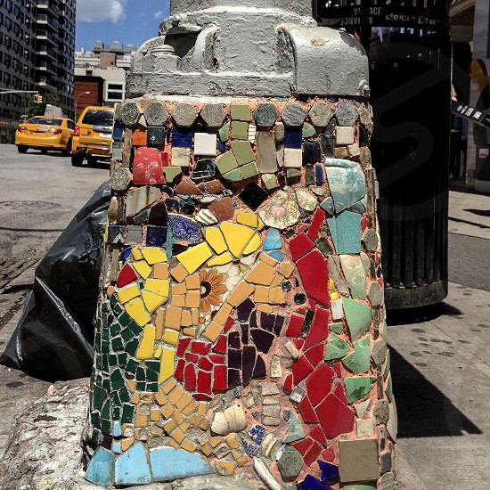 yellow blue and black mosaic artwork beside road photo