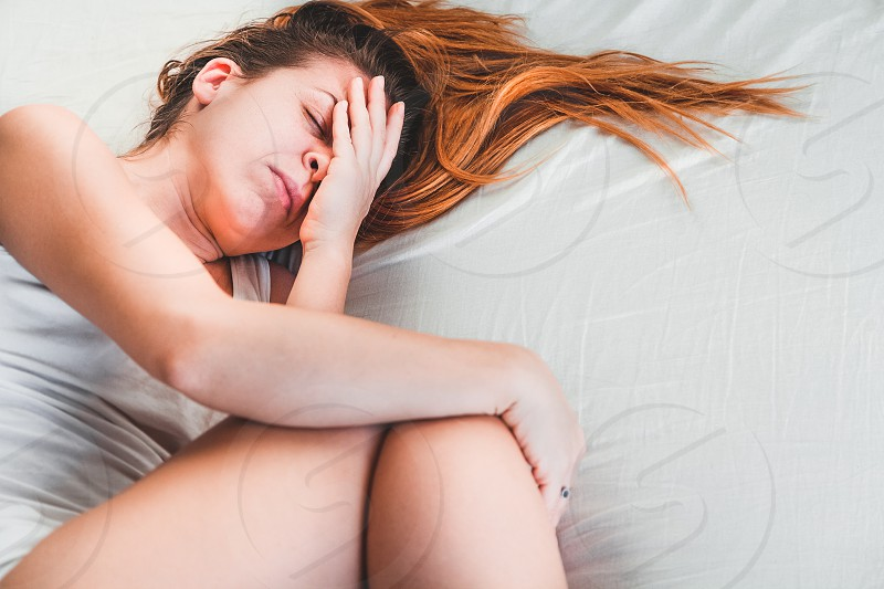 Young woman lying down in pain on the bed photo